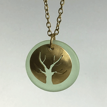 Tree Of Life Pendant in jewelers brass with etched pale aqua glass disk. Brass chain.