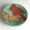 Small ceramic cardinal dish featuring a male cardinal on a turquoise blue background.