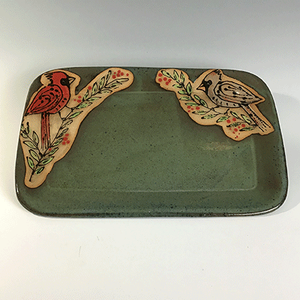 Rectangular ceramic tray featuring male and female cardinals in the upper corners on a green background.