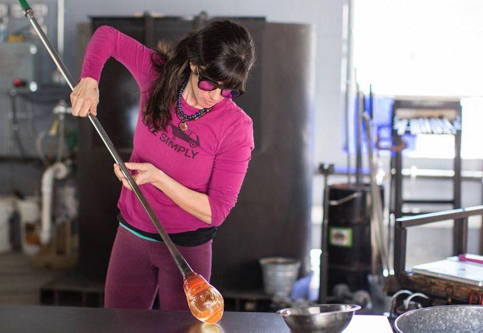 Jordana Korsen handblowing hot glass in her studio.